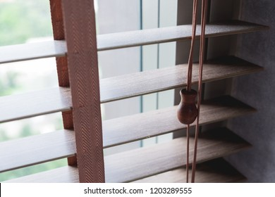 Close up photo of a wooden shutters blinds (Venetian blinds) with its rope