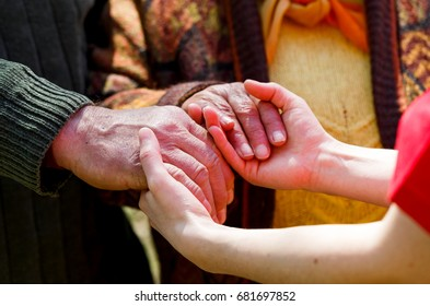 Close up photo of young caregiver holding elderly couple hands
