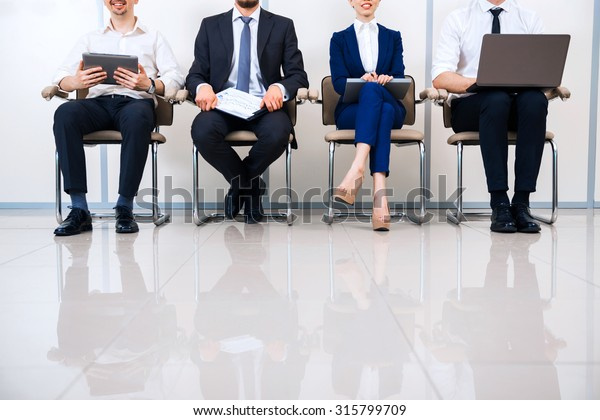 Close up photo of young creative business team of four with documents and computers. They sitting in a row and working