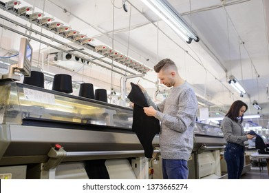 close up photo of a young man analyzing a piece of clothes and a woman working on industrial knitting machine