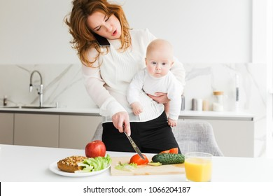 Close up photo of young mother standing and holding her little baby while talking on her cellphone and cooking on kitchen isolated
