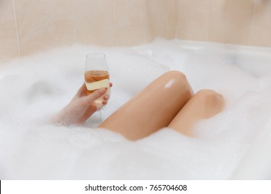 Close up photo of young sexy woman with straight naked body and clean legs lying and relaxing in white foam bath tub with candles around in light bathroom, drink alcohol from wine glass indoors