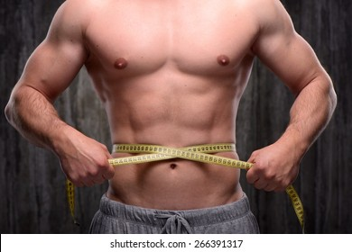Close up photo of young sporty man measuring his waist with yellow tape. Fitness concept
