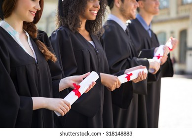 Close up photo of young students dressed in black graduation gown. Campus as a background. Students standing in row, smiling and holding diplomas