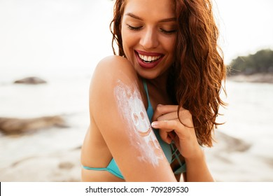 Close up photo of a young woman applying sunscreen protection cream at the beach.