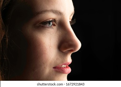 close up photo of a young woman crying with a tear coming down her cheek.