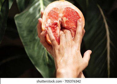 Close up photo of young woman hands holding half of grapefruit with big green leaves on background. Photo of hands showing cool gesture while holding grapefruit