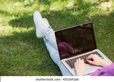 Close up photo of young woman outdoors. Woman using laptop. Beautiful green park as a background