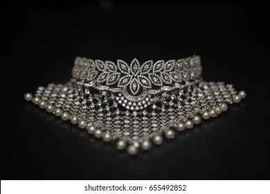 close up photograph of a diamond necklace lined with pearls in the end