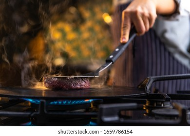 Close up photograph of a female chef grilling tasty, delicious, juicy burgers on a kitchen stove.