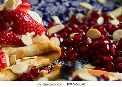 close up photograph of pomegranate seeds served next to crepe