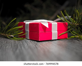 Close up photograph of a red small gift wrapped in white bow laying on a gray wood grain floor with evergreen pine needle limb in background.