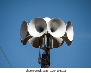 Close up photograph of several multi directional round amplified emergency siren  or noon time horns on top of a wooden pole in a small town in Wisconsin.