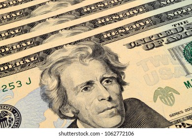 A close up photograph of twenty Dollar US notes with a portrait of Andrew Jackson.