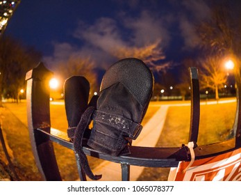 Close up photograph of two non-matching or mismatched different sized lost black colored mittens on top of a metal fence post awaiting their owners to claim them at night with street lights beyond.