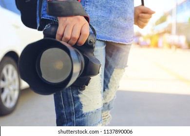 Close up of Photographer holding DSLR camera in his hands, Travel lifestyle vacations concept