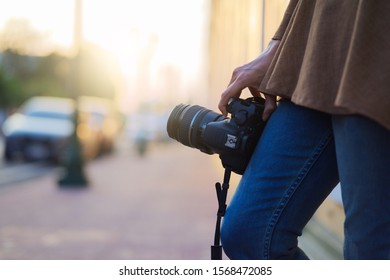 Close up Photographer standing and holding camera on hand with sunlight, photographer and camera lifestyle concept