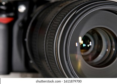 Close up of a photography camera lens as seen looking into the end of the lens with light reflection traveling down the lens and reflecting off the different pieces of glass