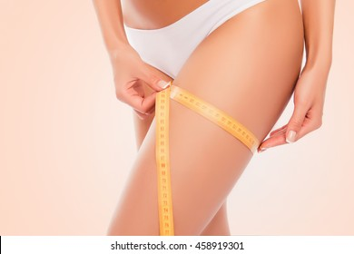 Close up photoof sexy woman measuring her leg's size with tape measure