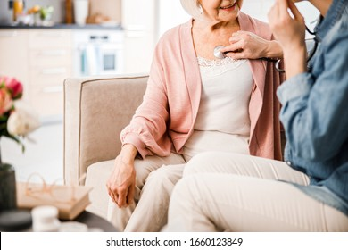 Close up of physician examining smiling senior lady with stethoscope stock photo