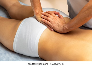 Close up of physiotherapist applying pressure on tailbone of female patient.