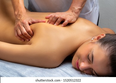 Close up of physiotherapist manipulating shoulder blade on young woman. Girl laying on spa bed with hands massaging shoulder.