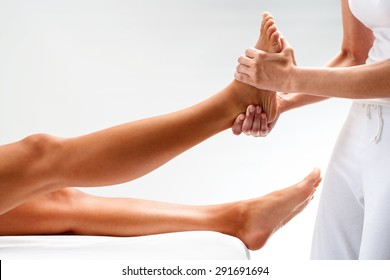 Close up of physiotherapist massaging female foot. Isolated on light background.