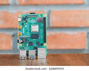 Close up of Raspberry​ pi 4 on wooden table with red brick background​