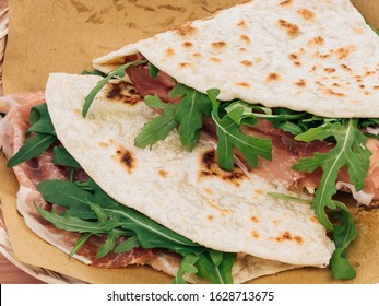 Close up of Piadina Romagnola. Fast italian food, take away food. Flat sandwich with ham and rucola