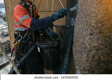 Close up pic of abseiler painter working at height abseiling twin nylon low stretch static rope wearing safety yellow helmet fall protection PPE harness using blue heavy duty glove while painting