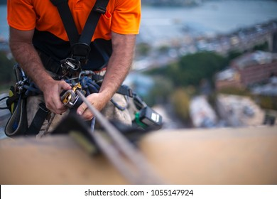 Close up pic of male rope access job industrial worker, using a safety device descender on static twin ropes abseiling, repairing windows at rise building in circular quay, Sydney city CBD, Australia