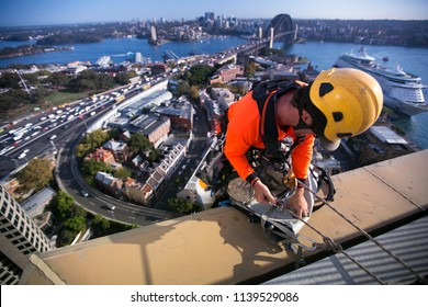 Close up pic of male rope access inspector  worker working at height and abseiling down from the high rise building site, with stunning harbour Sydney city CBD downtown view, Australia