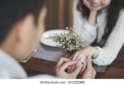 Close up pic of a young man's hand holding a sliver diamond engagement ring for the proposal to a young woman