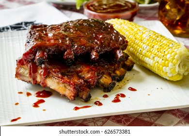 Close up of picnic table with plate whiskey bourbon barbeque pork ribs sitting on white plate with fresh corn on the cob