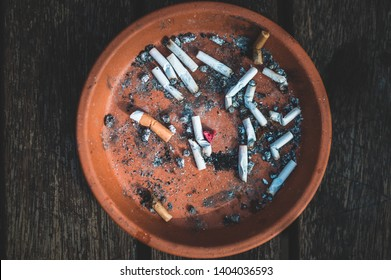 Close up picture of ashtray, full uf cigarettes and ashes. Dark desaturated colours, sad mood. Bad habits. Dark brown real wood table, Bright orange ashtray, dirty habit. Bad smell.