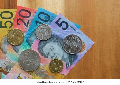 Close up picture of Australian banknotes and coins on a wooden table. Currency and money from Australia