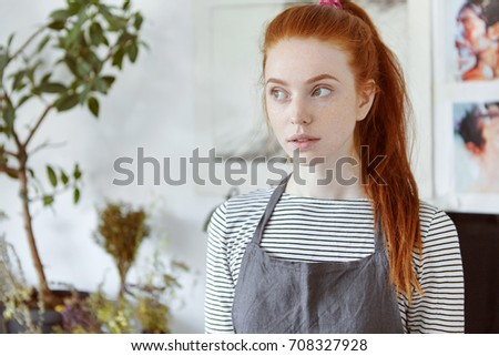 Close up picture of beautiful freckled red haired European girl student of arts school in college workshop with pictures on wall and plant in background, thinking over concept of her diploma project