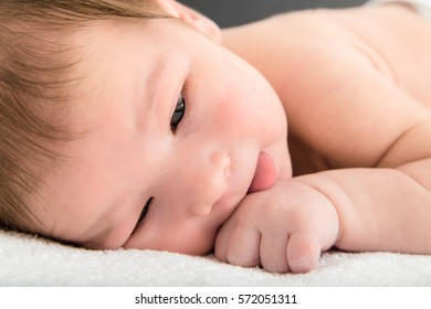 Close up picture of beautiful newborn baby resting on blanket leaning on hand , Cute little baby lying on soft bedspread in bedroom wearing diapers , Happy carefree childhood concept on dreamy ambient