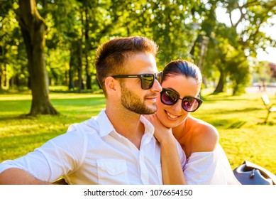 Close up picture of a beautiful young couple sitting on a bench with there sunglasses on in a park in the sunset