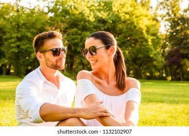 Close up picture of a beautiful young couple sitting on a field in a park in the sunset