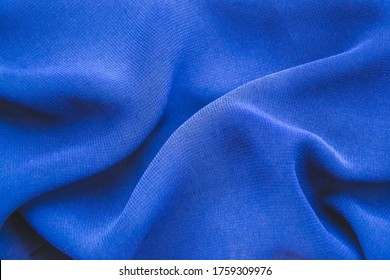 Close up picture of blue chiffon fabric with holds for fashion concept. Background with textured material and polyester structure. Macro photography of folded fabric for cloth design wallpaper.
