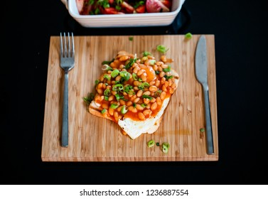 close up picture of breakfast. Tost, egg, beans, chives, on a wooden board, on a table. eating breakfast