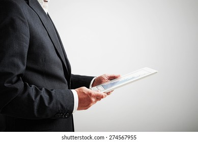 close up picture of businessman holding tablet pc with bar graphic