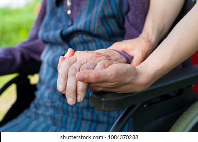 Close up picture of carer holding elderly woman's shaking hands, sitting in a wheelchair - Parkinson disease