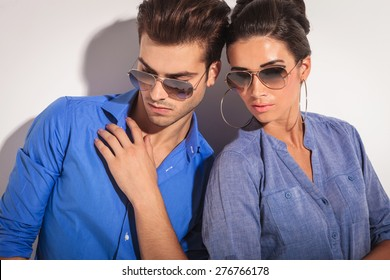 Close up picture of a casual fashion couple looking down, on studio background.