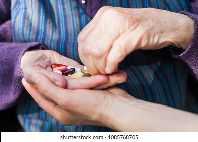 Close up picture of elderly disabled woman's hands receiving medical drugs from caregiver