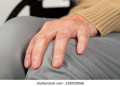 Close up picture of elderly female hand holding her knee -  sitting in a wheelchair, disabled