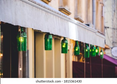 Close up picture of green bottle, as lights for cafe. Handmade lightning on the streets, as eco decoration. Illumination with wine bottles and empty space fro text. Background for restaurant.