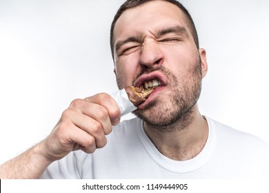 A close picture of guy eating sweet bar of chocolate with nouga. He is biting a big piece of this sweets. Young man is a fan of everythinf that is sweet. Isolated on white background.