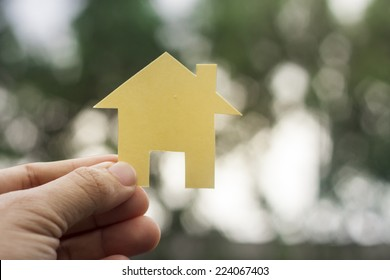 close up picture of hands holding house